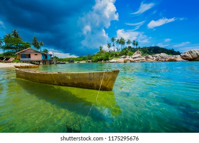 Traditional boats float above clear water in the fishing village of Trikora, Bintan Island