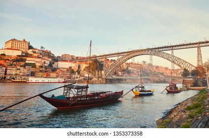 Traditional boats with wine barrels on Douro river in old Porto with background of Dom Luis bridge, Portugal