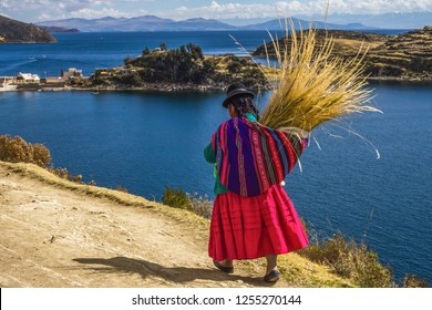 Traditional bolivian woman in traditional dress, walking trought the Sun island in lake titicaca, Bolivia