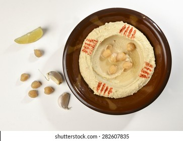 A traditional bowl of Hummus - an arabic chickpea paste, with garlic clove, lemon slice and chickpeas by side.