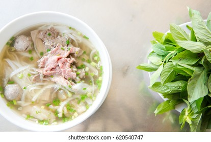 Traditional bowl of Vietnamese pho, beef noddle soup pho with fresh herbs, garnish of cilantro and Asian basil, lemon, lime, bean sprouts. Popular healthy street food of Asia.top view of a horizontal