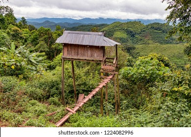 Traditional Boyhood Raised Hillside Hut in Indigenous Ethnic Minority Akha Village in Northern Laos with View of Mountain Horizon. (Akha Hill Tribe Village, Nam Ha Protected Area, Luang Namtha, Laos).