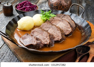 Traditional braised marinated German Sauerbraten from beef with potato dumplings and blue kraut in spicy brown sauce as closeup in a rustic wrought iron pan  - Shutterstock ID 1512917282