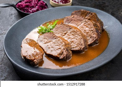 Traditional braised marinated German Sauerbraten from beef with blue kraut in spicy brown sauce as closeup in a modern design cast iron plate - Shutterstock ID 1512917288