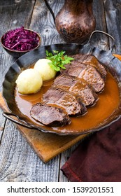 Traditional braised marinated German Sauerbraten from beef with potato dumplings and blue kraut in spicy brown sauce as closeup in a rustic wrought iron pan  - Shutterstock ID 1539201551