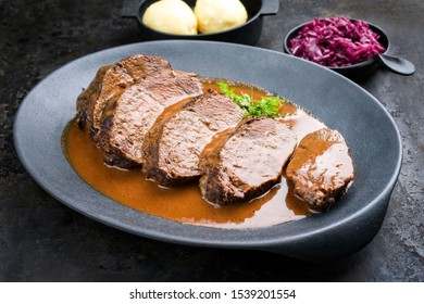 Traditional braised marinated German Sauerbraten from beef with blue kraut in spicy brown sauce as closeup in a modern design cast iron plate - Shutterstock ID 1539201554