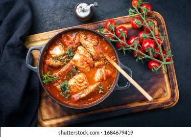 Traditioneller brasilianischer Fischeintopf Moqueca baiana mit Fischfilet in Tomatensauce als Draufsicht in einem modernen Design Gusseisen-Röstgericht