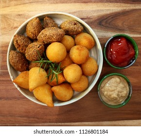 Traditional Brazilian snacks coxinha and quibe on wooden background. Top view.