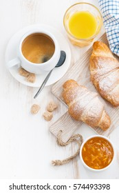 traditional breakfast with fresh croissants on white wooden background, top view, vertical