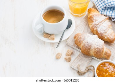 traditional breakfast with fresh croissants and white wooden background, top view, horizontal