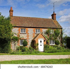 Traditional Brick and Flint English Village Cottage and garden with Climbing plants on the Wall