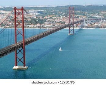 The traditional bridge over the river tagus (tejo), with a sailboat passing bellow. Lisbon, Portugal