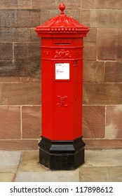 A traditional bright red cast iron British Victorian post or mail box
