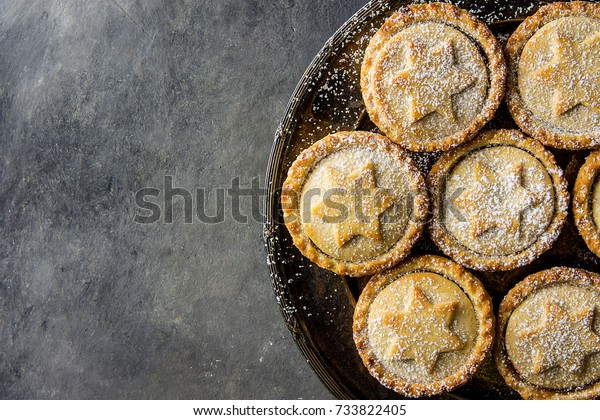 Traditional British Christmas Pastry Dessert Home Baked Mince Pies with Apple Raisins Nuts Filling Golden Shortcrust Powdered on Vintage Metal Plate Dark Concrete Background Top View Copy Space