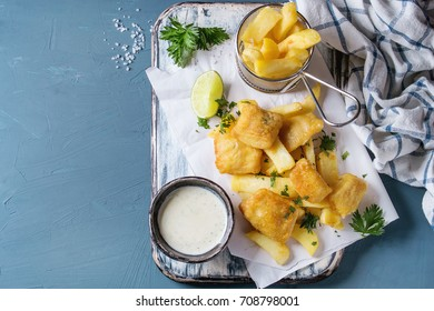 Traditional british fast food fish and chips. Served with white cheese sauce, lime, parsley, french fries in frying basket on white paper over blue concrete background. Top view, copy space.