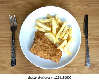 Traditional British fish and chips on wooden table, top view