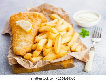 Traditional British Fish and Chips with tartar sauce on chopping board with fork and green peas on white stone background.