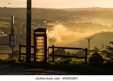 Traditional British Phone Box silhouetted against rural counltryside background.