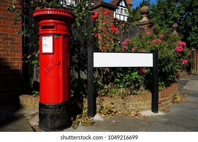Traditional British red post box with red pink rose flowers, copy space present. This free-standing type post box is found in the UK and members of the Commonwealth of Nations.