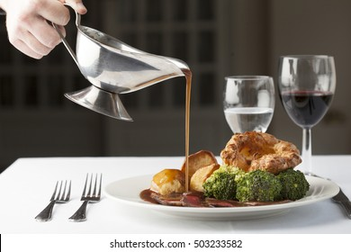 Traditional British roast dinner of rare beef, yorkshire pudding, roast potatoes and broccoli with gravy being poured over from a gravy boat.