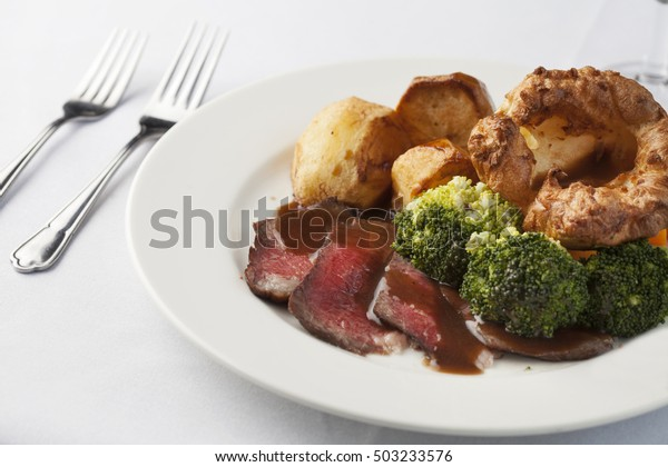 Traditional British roast dinner of rare beef, yorkshire pudding, roast potatoes and broccoli with gravy.