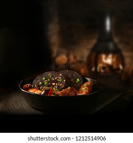 Traditional British savoury dish of Black Pudding with sauasages and grilled vine tomatoes in a wrought iron skillet shot against a rustic background with a roaring wood burner. Copy space.