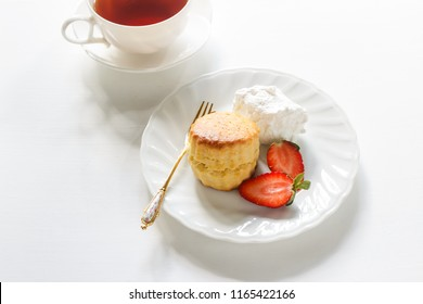 Traditional British Scones with clotted cream, fresh strawberry with cup of tea.
