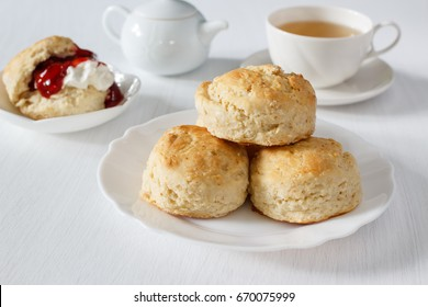 Traditional British Scones with clotted cream, strawberry jam and a cup of tea.
