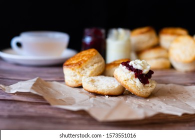 Traditional British Scones with Cream cheese, Cranberry jam and a cup of tea on wooden table black background.