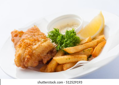 Traditional British style fish and chips including deep fried cod, french fries, lemon, and tartar sauce in ceramic dish