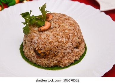 Traditional broken wheat biryani/pilaf/ biriyani/biriani, is an Indian mixed rice dish prepared using Indian masalas. Healthy food made of whole wheat, low in calaories Kerala, India