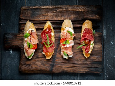 Traditional Bruschetta with Parma dried ham and prosciutto. Italian antipasti set sandwiches with jamon, cottage cheese, arugula, and sun-dried tomatoes on a rustic wooden Board Top view