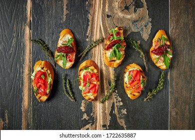 Traditional Bruschetta with Parma dried ham and prosciutto. Italian antipasti set sandwiches on a rustic wooden Board Top view
