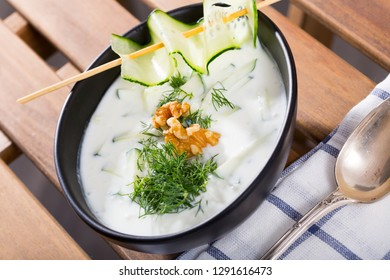 Traditional Bulgarian cold vegetable soup Tarator with cucumber, walnuts, garlic and yogurt in black bowl