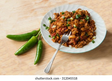 Traditional Bulgarian food - mish mash (baked pepers, scrambled eggs and onion) with green chili - wood background
