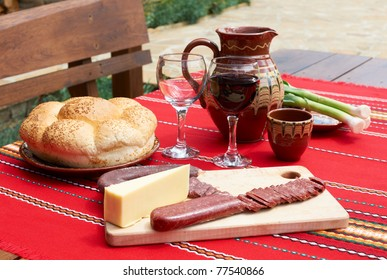 Traditional Bulgarian food wine, saussage and yellow cheese on rural table