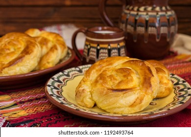 Traditional Bulgarian homemade banitsa spiral phyllo pastry with cheese in ceramic plates on red tablecloth.