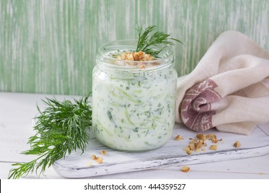 Traditional Bulgarian sour milk soup, tarator, with yogurt, cucumbers, walnuts and dill in a glass jar, selective focus