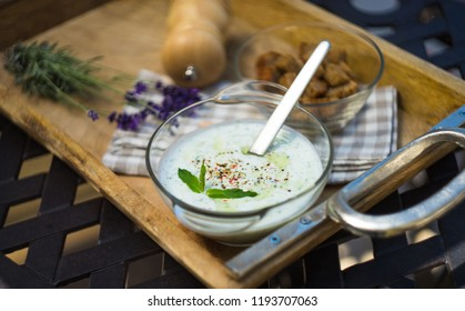 Traditional bulgarian summer cold soup Tarator with cucumber, yogurt and dill on rustic background with copy space