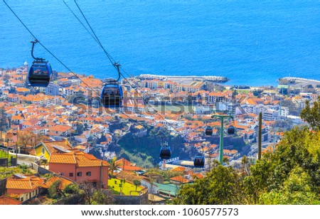 Traditional cable car transporting tourists above Funchal city of Madeira island, Portugal