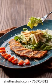 Traditional Caesar grilled chicken salad with vegetables and cheese. Asian oriental cuisine. Restaurant menu.