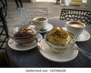 Traditional Calabrian Tartufo ice cream in cross-section with nougat filling at a cafe in Pizzo, chcocolate nougat and pistachio ice cream balls and cappuccino cups on a table infront of a cafe
