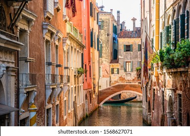 Traditional canal street with gondolas and boats in Venice, Italy.