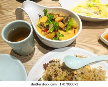 The traditional Cantonese cuisine. There are curry beef, poached vegetable, egg fried rice, a cup of black tea and a dish of plum sauce on the table.