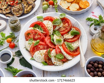 Traditional Caprese salad made of sliced fresh tomatoes, mozzarella cheese and basil  served on a white plate on a wooden table, top view