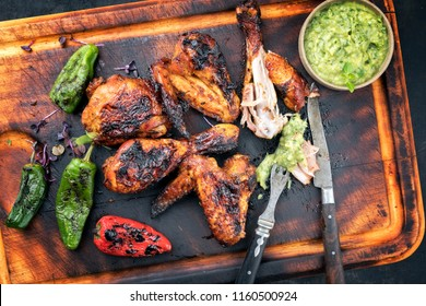 Traditional Caribbean barbecue jerk chicken wings and drumsticks with chimichurri sauce, jalapeno and poblano chili as top view on an old wooden cutting board