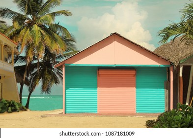 Traditional caribbean styled colorful wooden log cabin, pink and blue, warm pastel toned, on coast with seaview and palms behind.