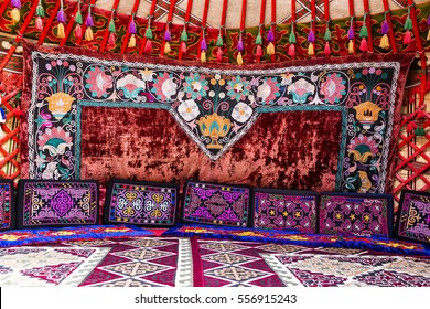 Traditional carpet, rug and pillow treatment details in the interior of a nomadic yurt