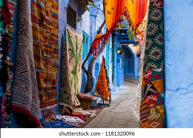 Traditional carpets in colorful narrow street of Chefchaouen in Morocco