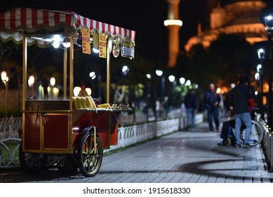 Traditional cart of Turkish street food in night near of Blue Mosque. Text on signboards in translation from Turkish language on English - Corn in the embers and milk corn.